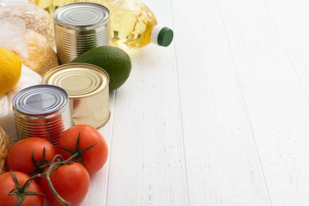 흰색 나무 테이블에 토마토, 캔, 아보카도 및 더 많은 음식