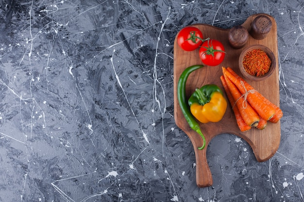 Tomatoes, carrots and different peppers on wooden cutting board.