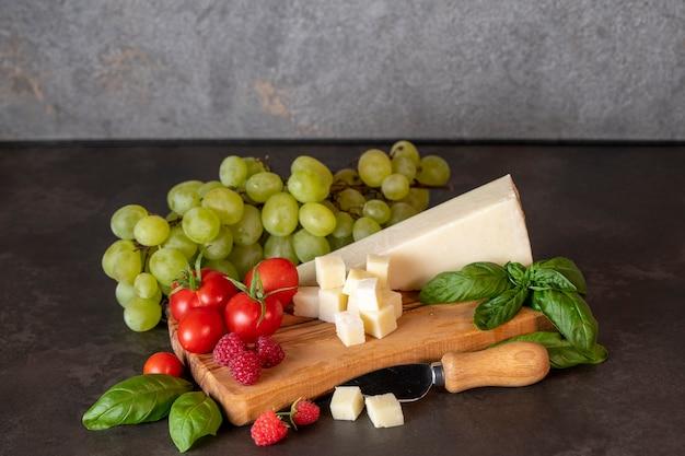 어두운 배경에 있는 올리브 보드에 토마토, 치즈, 바질, 라즈베리, 포도