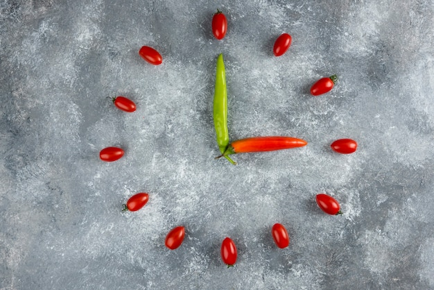 Tomatoes and chilli peppers formed like clock on marble surface.