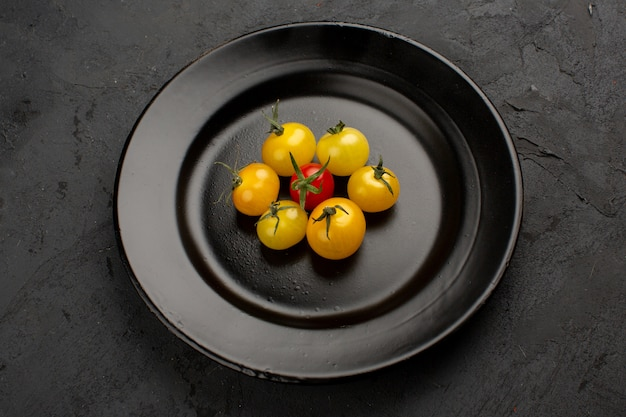 Tomatoes colorful fresh ripe inside black plate on a grey