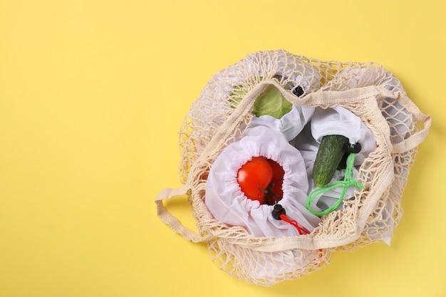 トマト、きゅうり、キャベツの再利用可能なメッシュバッグ、明るい黄色の背景の大きなメッシュバッグ。生態学的概念。汚染を止めなさい。ゼロウェイストショッピング。コピースペース