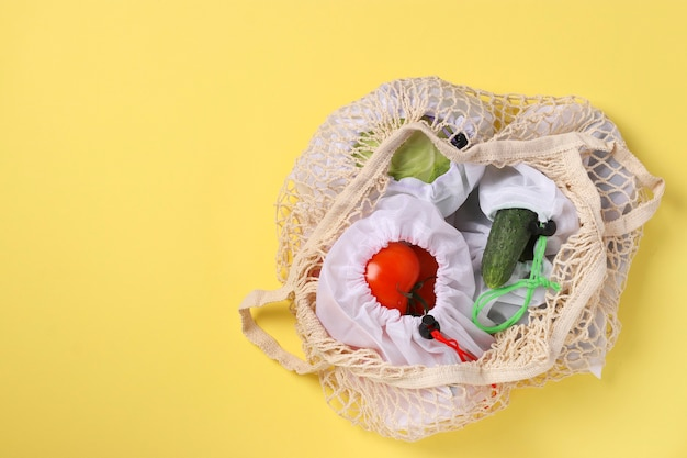 Tomatoes, cucumbers, cabbage in reusable mesh bags, in a large mesh bag on bright yellow background. ecological concept. stop pollution. zero waste shopping. copy space
