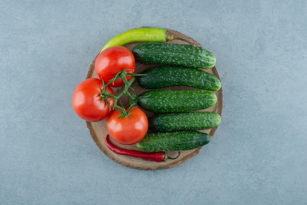 Tomatoes, cucumbers and pepper on wooden piece.