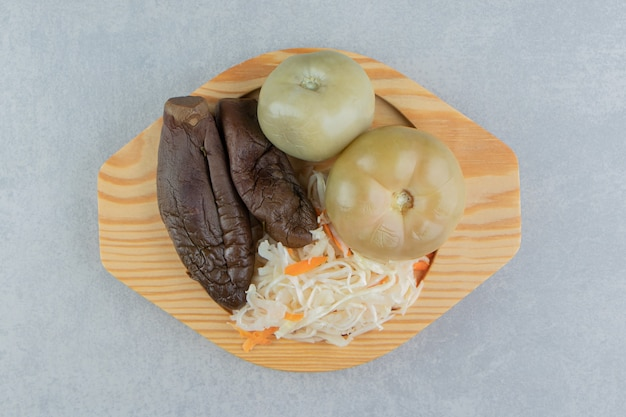 Помидоры, баклажаны и квашеная капуста в деревянной тарелке на мраморной поверхности