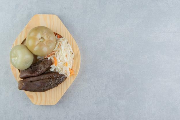 Помидоры, баклажаны и квашеная капуста на деревянной тарелке