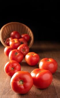 木の表面のバスケットから落ちてくるトマト