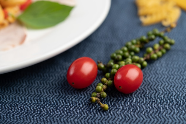Tomatoes and fresh pepper seeds on patterned fabric.