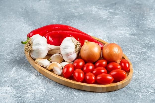 Помидоры, чеснок и перец на деревянной тарелке.