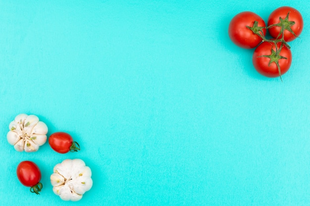Tomatoes and garlic concept with copy space top view on light blue surface