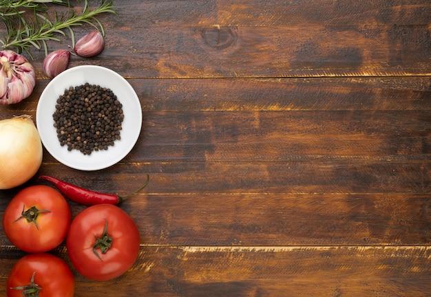 Помидоры, чеснок, перец и травы над деревянным столом с местом для текста.
