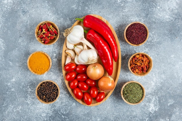 Tomatoes, garlic and peppers on wooden plate with spices.