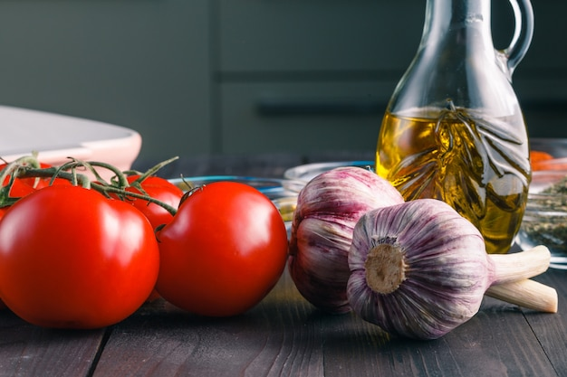 Tomatoes and garlic on wooden black table  surface