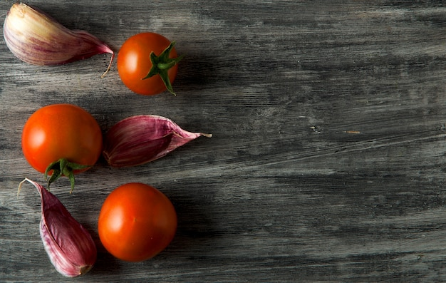 Tomatoes, garlic on a wooden surface.