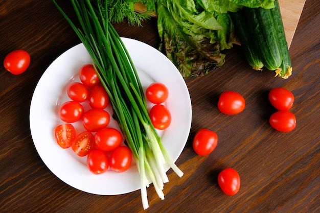 Tomatoes and green onions on a plate
