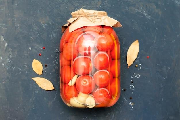 黒い壁、上面図のガラスの瓶にトマト。自家製ブランク、缶詰。