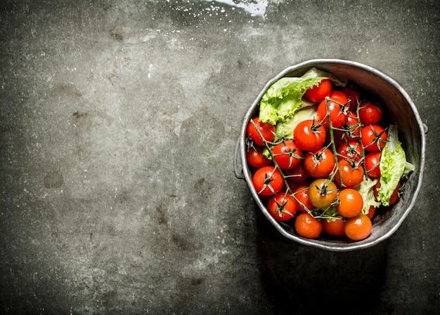 古い鍋のトマト。濡れた石の背景。