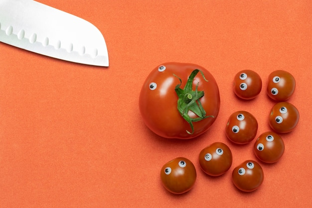 Tomatoes and knife with eyes, funny kitchen concept, copy space