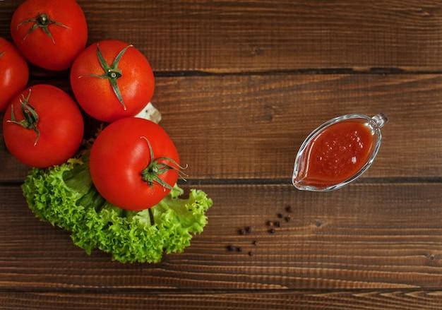 Помидоры, салат и соус. вид сверху. здоровое питание и вегетарианство.
