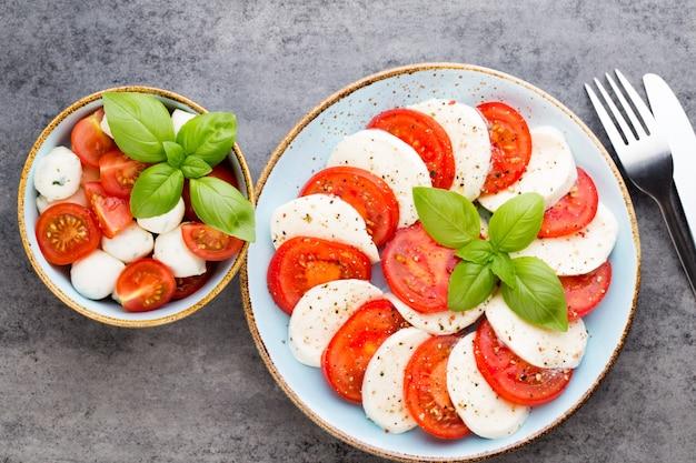 Помидоры, сыр моцарелла, базилик и специи на доске из серого сланца. ингредиенты итальянского традиционного салата капрезе. средиземноморская кухня.