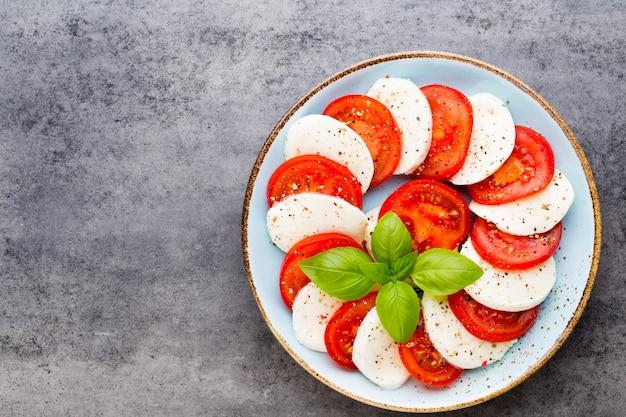 トマト、モッツァレラチーズ、バジル、スパイス、灰色のスレートの石の黒板。イタリアの伝統的なカプレーゼサラダの材料。地中海料理。