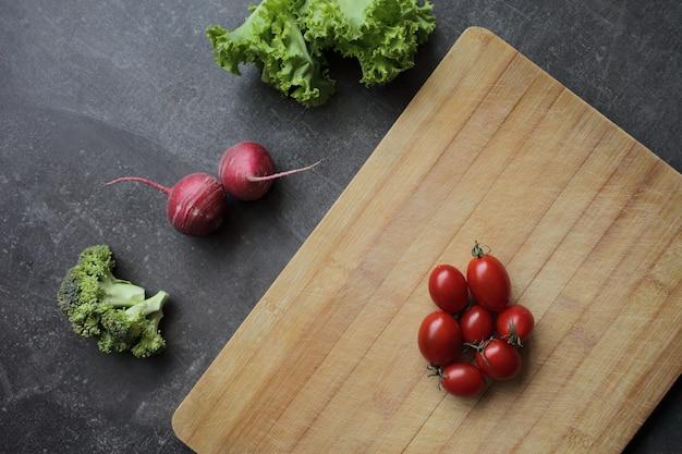 灰色のテーブルと新鮮な野菜のまな板の上のトマト