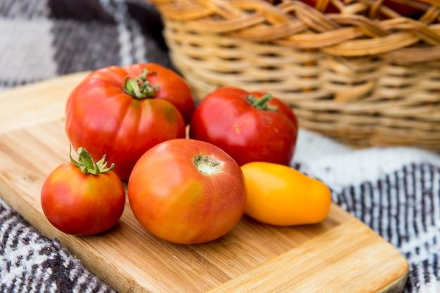板の上のトマト。秋までに収穫。トマトの大きなバスケットを背景に。