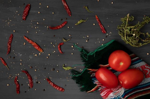 乾燥唐辛子と灰色の背景に唐辛子とテーブルクロスのトマト