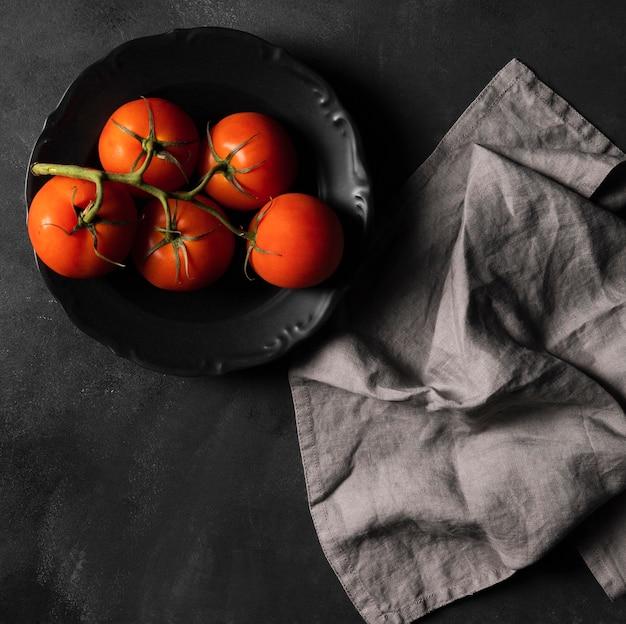 Помидоры на тарелке и ткани