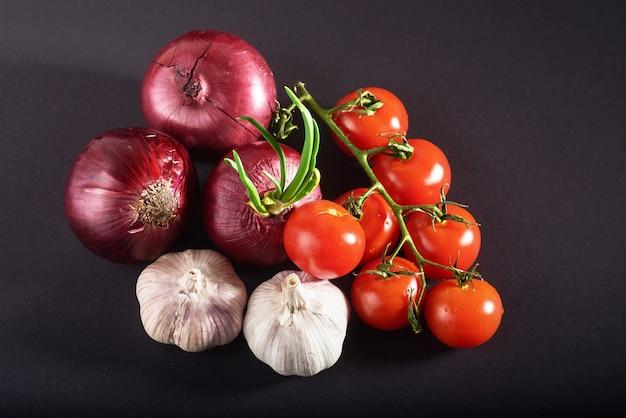 Pomodori, cipolle e aglio sono isolati su un nero