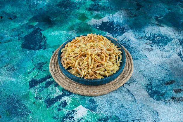 青い背景に、バケツにトマト、コショウ、自家製麺。
