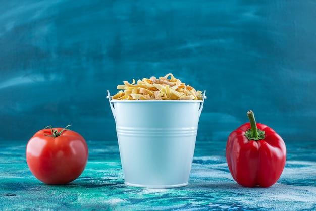 Pomodori, pepe e pasta fatta in casa in un secchio, sul tavolo blu.