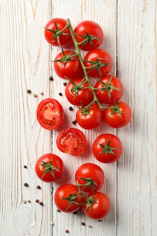 Tomatoes and pepper on wooden background, top view