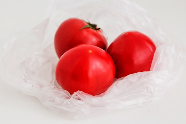 Tomatoes in a plastic bag on a light background