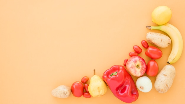 Tomatoes; potatoes; pears; banana; apple and lime on beige background