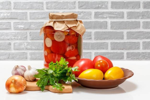 Помидоры консервированные в стеклянной банке, свежие помидоры, листья петрушки, чеснок, лук на кухонном столе.