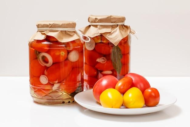 유리병에 보존된 토마토와 접시에 신선한 토마토. 흰색 바탕에 절인된 토마토입니다. 수제 보존제.