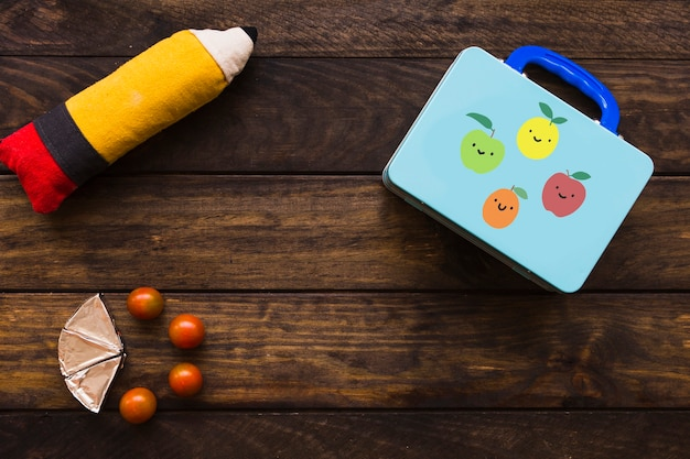 Tomatoes and processed cheese near lunchbox and pencil case