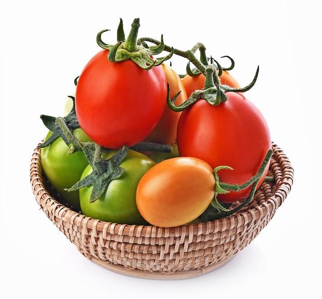 白い背景の上のバスケットのトマト赤、緑、黄色