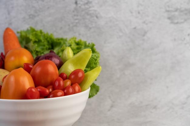セメントの床に白いカップにトマト、赤玉ねぎ、ピーマン、ニンジン、白菜。