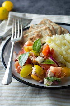 Tomatoes salad and mashed potatoes in a plate