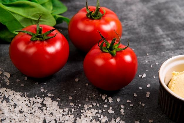 Pomodori, sale e verdure su superficie di legno grigio