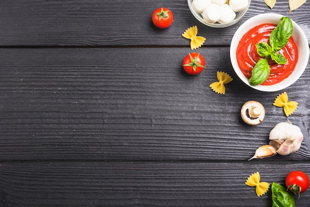 Tomatoes sauce with ingredients on black wooden plank