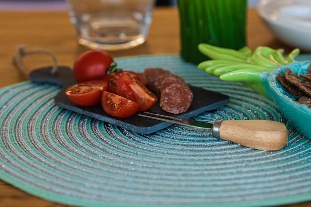 Помидоры, сырые колбаски, печенье в тарелке и зеленая травка свечи на кухне