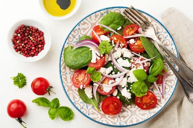 軽いセラミック プレートにトマト、ほうれん草の葉、赤玉ねぎ、フェタ チーズのサラダ。選択と集中。上面図。