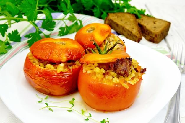 肉と蒸し小麦のブルグルを詰めたトマト、プレートにタイムの小枝、ナプキン、フォーク、パン、パセリを背景に明るい木の板