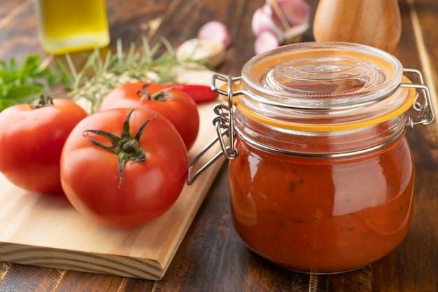 Помидоры, томатный соус, чеснок, перец и зелень над деревянным столом.