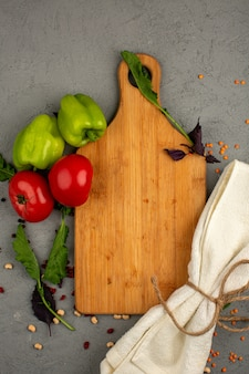 Pomodori una vista dall'alto di peperoni freschi maturi e verdi freschi rossi con erbe verdi e scrivania su una luce