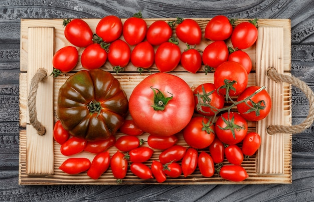 Tomatoes variety in a rustic handmade tray on a wooden grey wall. flat lay.