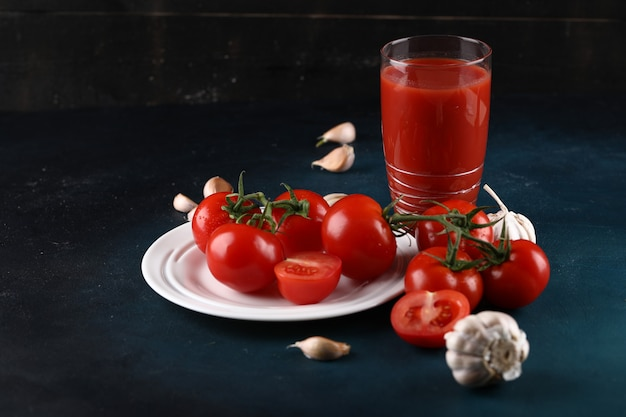 Tomatoes in white plate with garlic gloves and a glass of tomato juice.